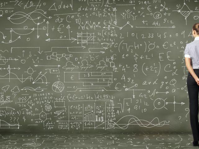 woman examining blackboard